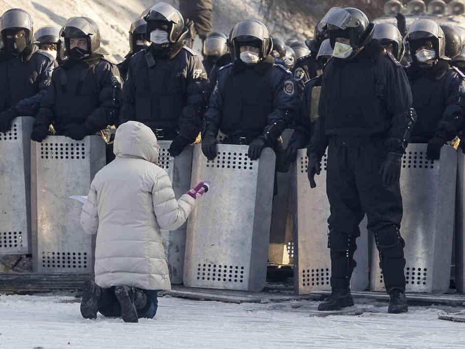 A protestor prays in the path of Ukrainian police who are advancing on the pro-democracy  demonstrators.