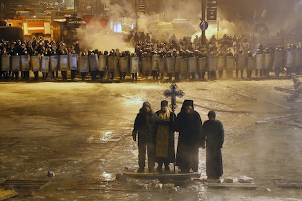 Ukrainian Orthodox priests pray as they stand between pro-democracy activist and police lines in central Kiev, Ukraine.