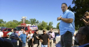 Joe Costephens, pastor of The Passage, located in suburban St. Louis, talks to Ferguson, Mo., residents during a cleanup project. Costephens and other St. Louis church planters organized the project to help the community after rioting and looting occurred Sunday evening.