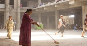A Iraqi Christian refugee sweeping the concrete floor of the unfinished building where she now lives. Ankawa; August 20 2014