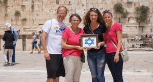 Here, Anita and Emma hold a Star of David, sewn and framed by Anita's mom while Anita visited Israel for the first time in the  1980s. Pictured left to right, Dwight, Anita, Emma and Hannah Widaman.
