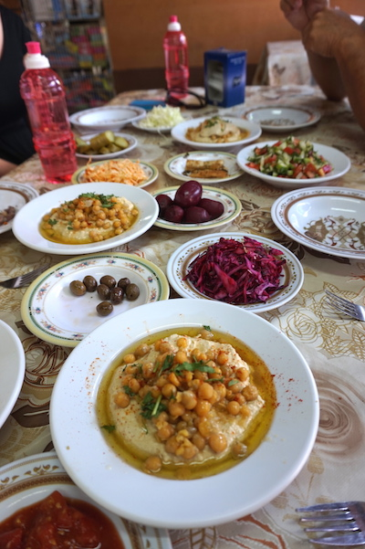 "A typical Israeli lunch includes pita bread with hummus- a mashed chickpea spread; Falafel- deep fried balls of chickpeas, onions and some other ingredients, usually served in pita bread; Shnitzel- fried chicken cutlets, served with hummus and ketchup; Baba Ganoush- an eggplant spread and often Shwarma: grilled meat, typically lamb, which is usually ""shaved"", often enjoyed in pita or laffa bread. Add to that various fresh pickled vegetables, all served family style. It's a colorful table that encourages conversation."