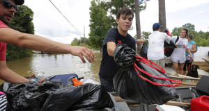 A resident transfers his belongings into a boat after being rescued in Ascension Parish, Louisiana, on August 15, 2016. Photo courtesy of REUTERS/Jonathan Bachman