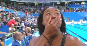 An emotional Simone Manuel looks up at teammates after she tied for gold in the women's 100-meter freestyle swim. Manuel is the first African American woman to medal in an individual swimming event.