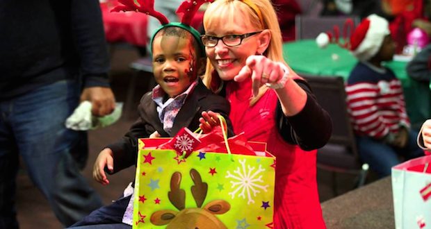 A Prison Fellowship volunteer helps a youngster open Christmas gifts through the Angel Tree program. Angel Tree works with children who have an incarcerated parent.