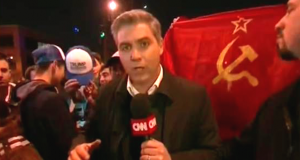 Anti-Trump protesters, carrying the Communist flag, march behind a CNN reporter.
