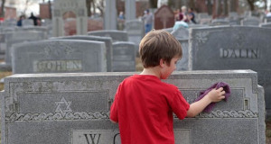 A young volunteer cleaned headstones in a Jewish Cemetery after vandals destroyed hundreds.